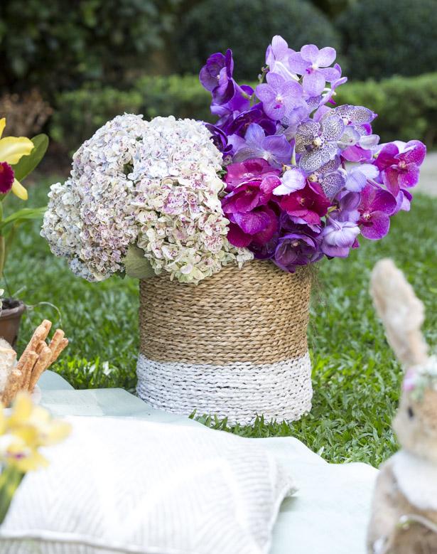 cestos de palha com alça com hortênsias e orquídeas em tons de lilás e roxo