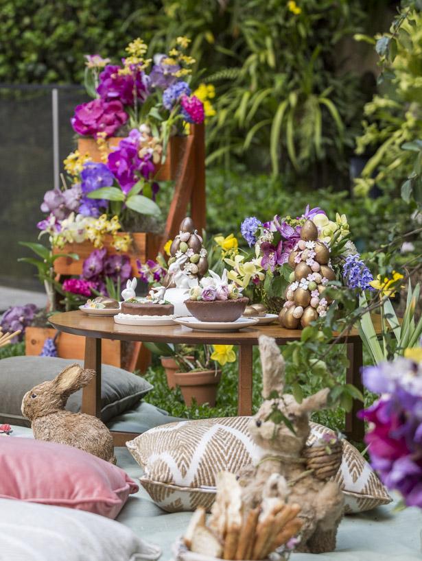 mesa de madeira com chocolates da coleção de Páscoa daPati Piva, enfeites e flores.