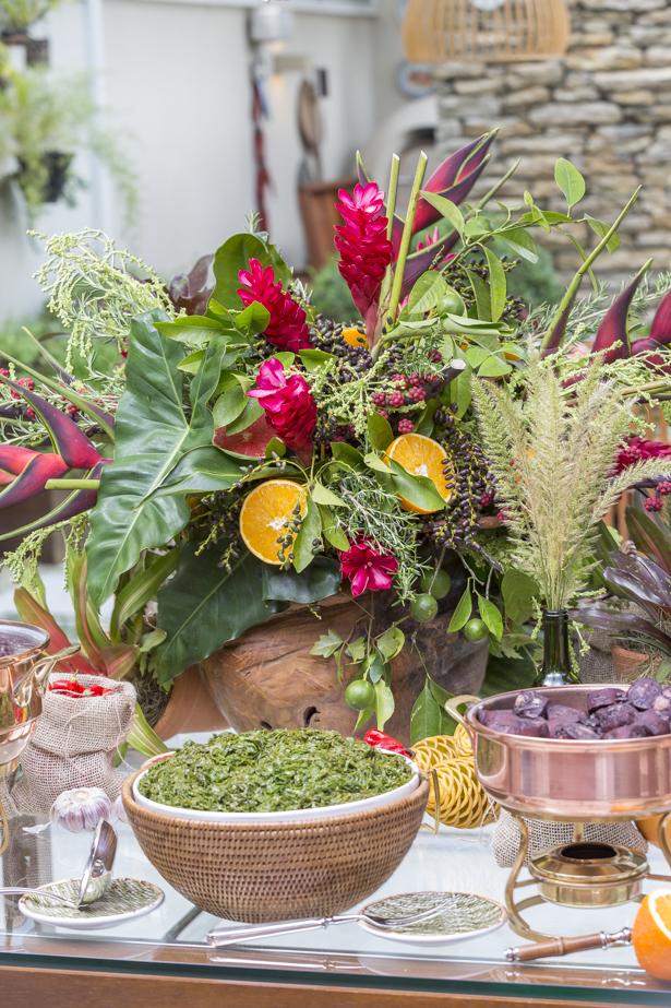 mesa buffet com decorada com flores tropicais para servir feijoada