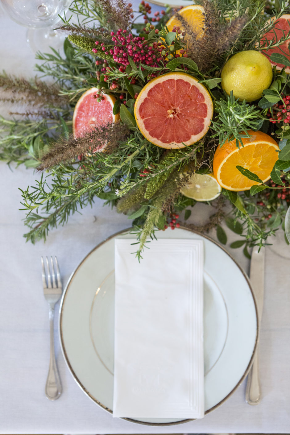 mesa posta com louça branca e arranjo colorido para churrascada