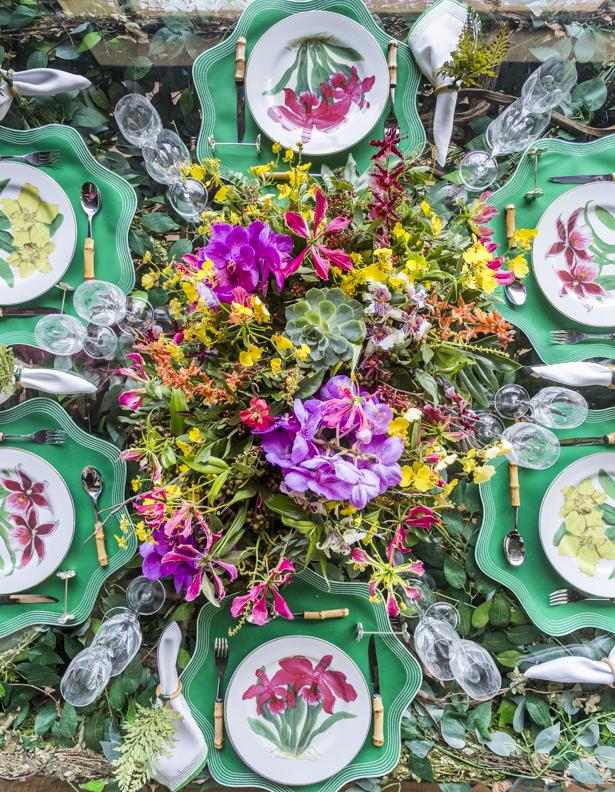 mesa posta decorada com folhagem e arranjo colorido